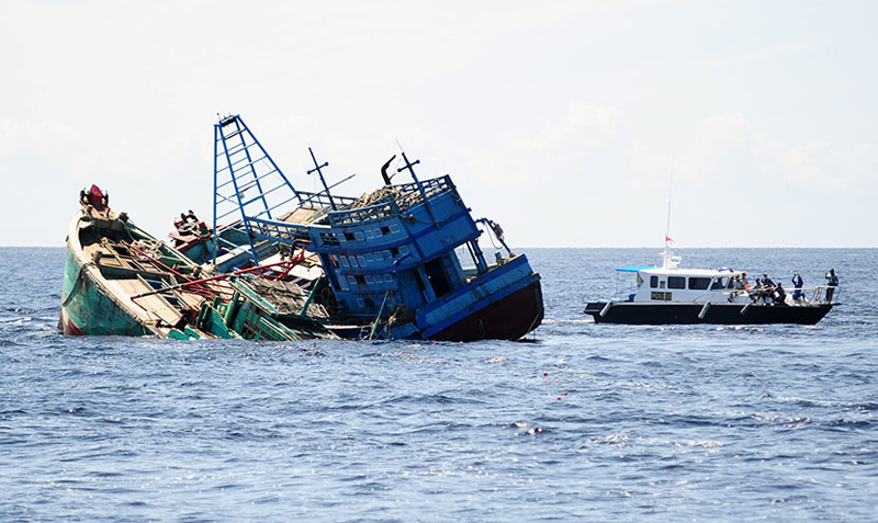 Kapal Polisi Air (Polair) berada di samping dua kapal motor nelayan Vietnam yang ditenggelamkan di Pulau Datuk, Kabupaten Mempawah, Kalbar, Selasa (5/4). Kementerian Kelautan dan Perikanan bersama Polri menenggelamkan dua kapal Vietnam yaitu KM Sinar-288/BV3240TS dan KM Sinar-533/BV99253TS yang ditangkap Kapal Patroli Pinguin-5011 dari Ditpolair Mabes Polri saat sedang mencuri ikan di Perairan Pulau Sumpadi, Kabupaten Sambas, Kalbar pada Maret lalu. ANTARA FOTO/Jessica Helena Wuysang/aww/16.